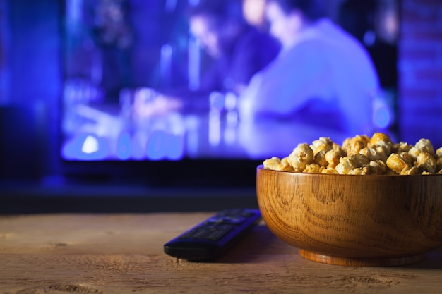 Una ciotola di legno di popcorn e telecomando.