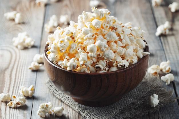 Una ciotola di legno di popcorn salato al vecchio tavolo di legno