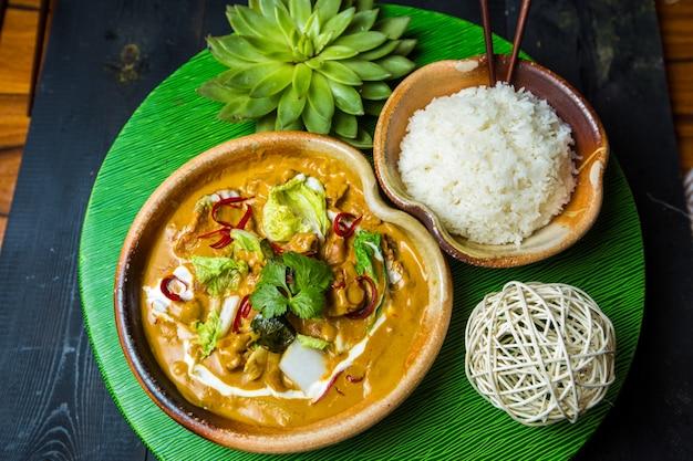 Una ciotola di pollo cinese al curry e ciotola di riso