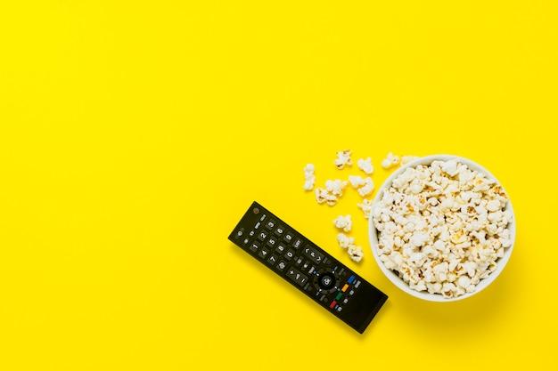 Una ciotola di popcorn e telecomando tv su uno sfondo giallo. il concetto di guardare la tv, film, serie tv, sport, spettacoli. vista piana, vista dall'alto.