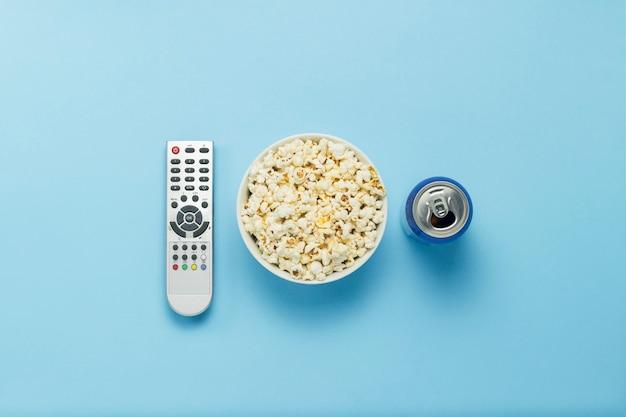 Una ciotola di popcorn, un telecomando della tv, una lattina con un drink su sfondo blu. il concetto di guardare la tv, film, serie tv, sport, spettacoli. vista piana, vista dall'alto.