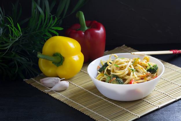 Una ciotola di soffriggere tagliatelle di udon con verdure e salsa di soia su una stuoia di bambù