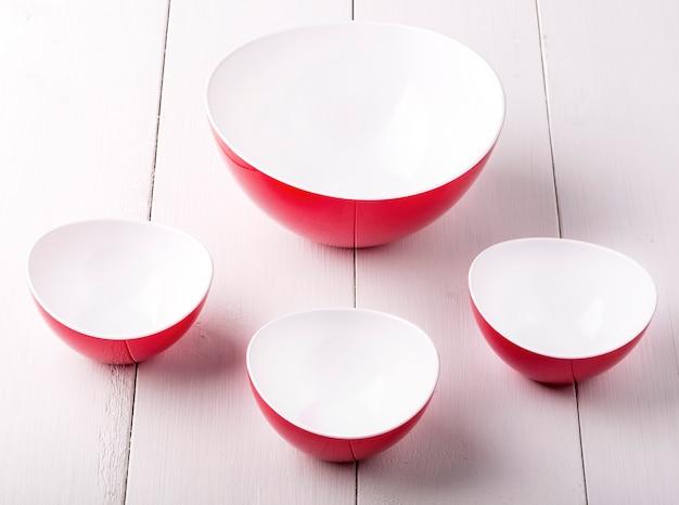 Una ciotola e tazze di insalata rosse vuote su una tavola di legno bianca