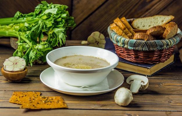 Una ciotola in ceramica bianca di zuppa di funghi servita con guanti all'aglio