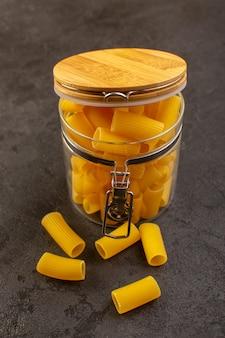 Una ciotola interna cruda gialla gialla della pasta asciutta di vista frontale isolata sul buio