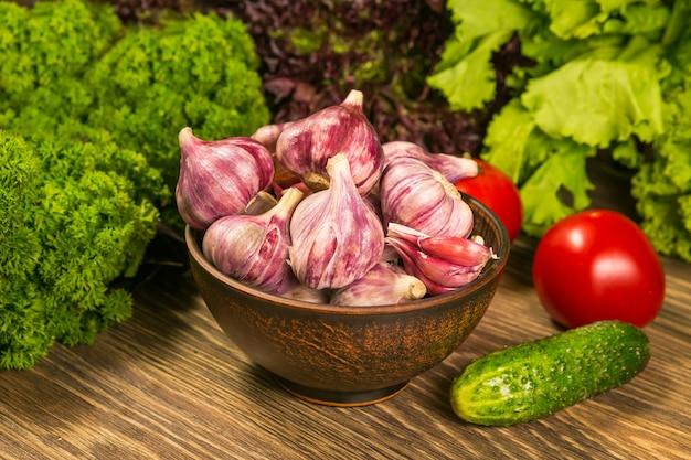 Una ciotola piena con bulbi d'aglio. pomodori e cetrioli su un tavolo di legno. insalata verde in background.