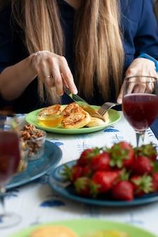 Una colazione gourmet per due: syrnyky, fragole, succo d'uva e vari antipasti.