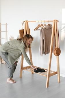 Una collezione di abiti, nei toni del beige, appesi a una gruccia nel camerino. materiale naturale. la donna sceglie abiti eleganti.