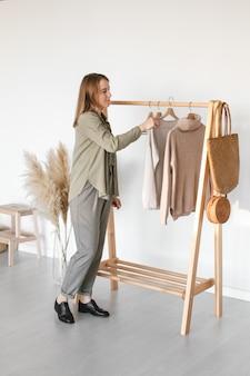 Una collezione di abiti, nei toni del beige, appesi a una gruccia nel camerino. materiale naturale.