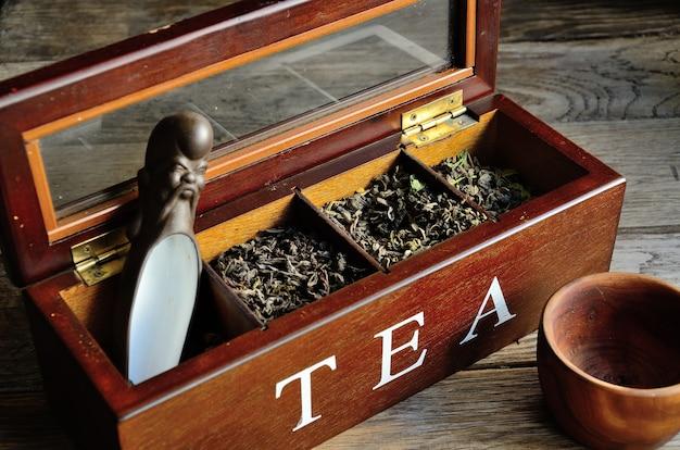 Una collezione di tè in una scatola di legno, un bicchiere di legno con un cucchiaino stilizzato su uno sfondo di legno.