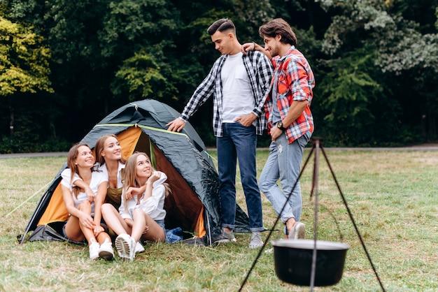 Una compagnia di amici accanto alla tenda. - concetto di campeggio