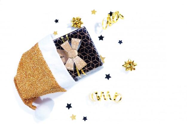 Una confezione regalo nera con un motivo geometrico e un fiocco dorato cade da un cappello di natale bianco-dorato, stelle, caramelle, serpentine, fiocchi su bianco