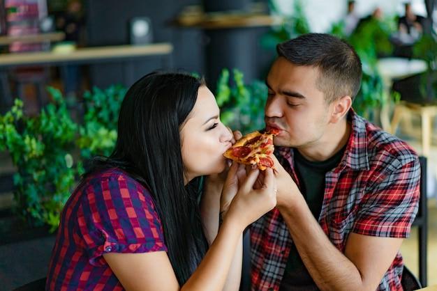 Una coppia abbastanza giovane che mangia insieme una fetta di pizza. una ragazza simpatica e un bell'uomo che morde la stessa pizza in un moderno caffè.