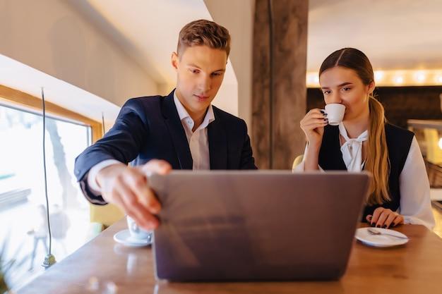 Una coppia alla moda beve caffè mattutino al caffè e lavora con un computer portatile