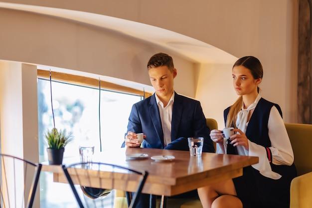 Una coppia alla moda beve caffè mattutino al caffè, giovani uomini d'affari e liberi professionisti