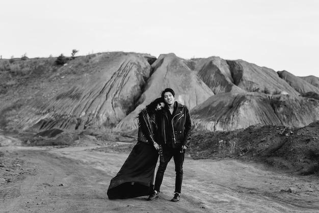 Una coppia asiatica innamorata in abiti di pelle nera cammina nella natura tra gli alberi. nero bianco