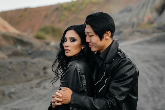 Una coppia asiatica innamorata in abiti di pelle nera cammina nella natura tra gli alberi. stile, moda, amore