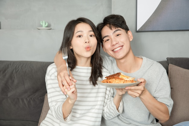 Una coppia cinese stava riposando e mangiando sul divano.