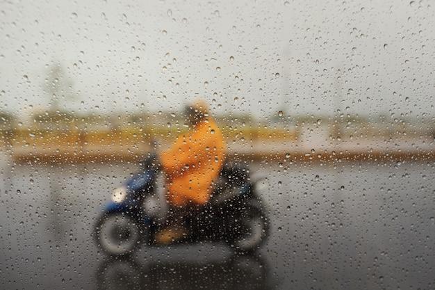 Una coppia con l'impermeabile su una moto durante le forti piogge. messa a fuoco selettiva e composizione di profondità di campo molto bassa.