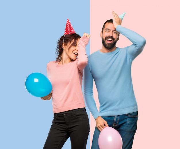 Una coppia con palloncini e cappelli di compleanno ha appena realizzato qualcosa e ha intenzione di farlo