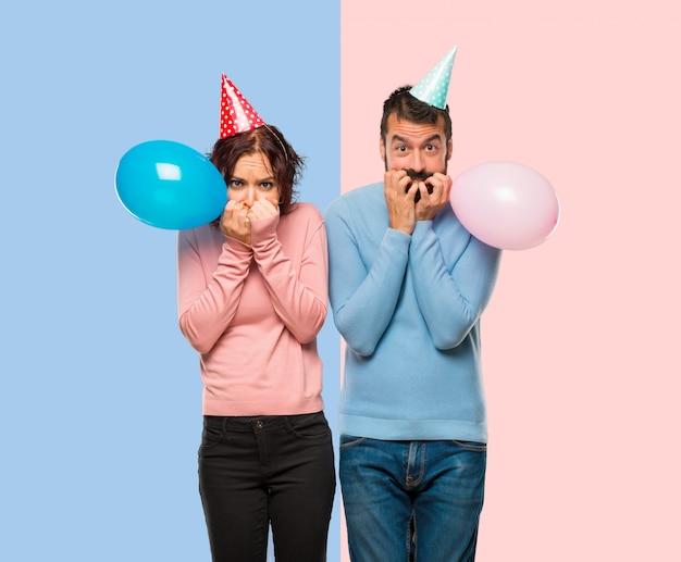 Una coppia con palloncini e cappelli per il compleanno è un po 'nervosa e spaventata a cui mettere le mani