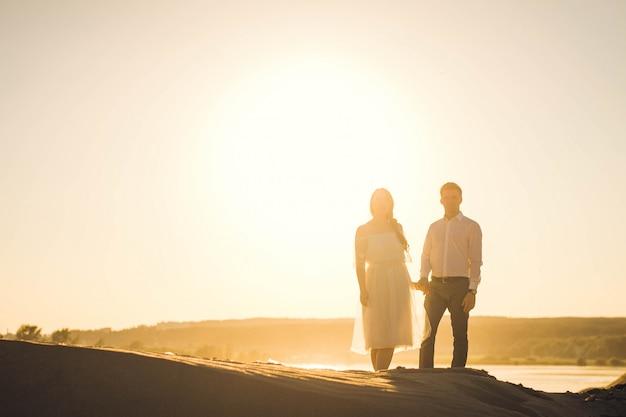 Una coppia di amanti si tiene per mano. silhouette di vlaenne contro il sole. coppia fuori fuoco.