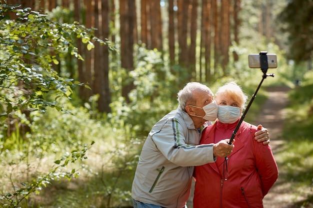Una coppia di anziani in maschere protettive fa un selfie su uno smartphone e cammina nel parco