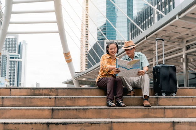 Una coppia di anziani turisti asiatici che visitano felicemente la capitale e si divertono e guardano la mappa per trovare luoghi da visitare.