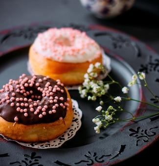 Una coppia di ciambelle con crema al cioccolato in cima
