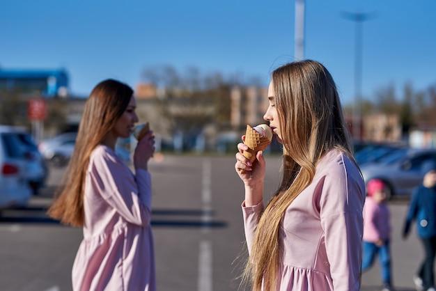 Una coppia di due belle donne o ragazze piuttosto sexy che mangiano il gelato per strada, abiti rosa