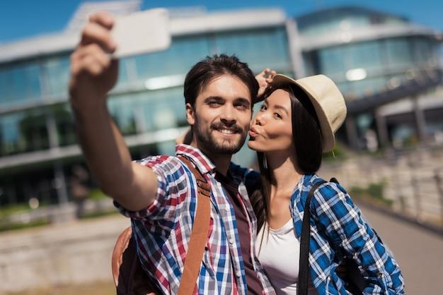 Una coppia di giovani turisti fa selfie.