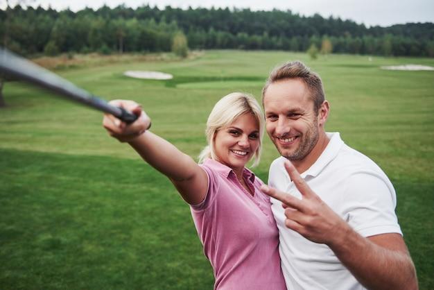 Una coppia di golfisti fa una foto sul campo da golf usando un bastone come un palo sephi