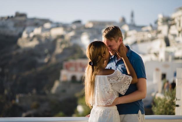Una coppia di innamorati cammina per le strade della città vecchia sull'isola di santorini.