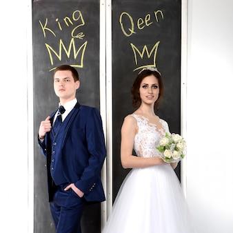 Una coppia di innamorati con corone e iscrizioni è il re e la regina. la sposa con lo zhinyh vicino al tabellone con iscrizioni il re e la regina.