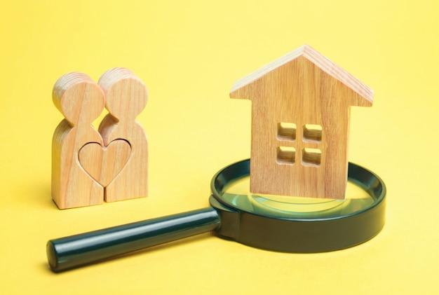 Una coppia di innamorati è in piedi vicino alla casa e una lente d'ingrandimento.