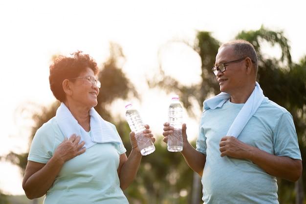 Una coppia di uomo anziano asiatico e donna facendo esercizio fisico all'aperto