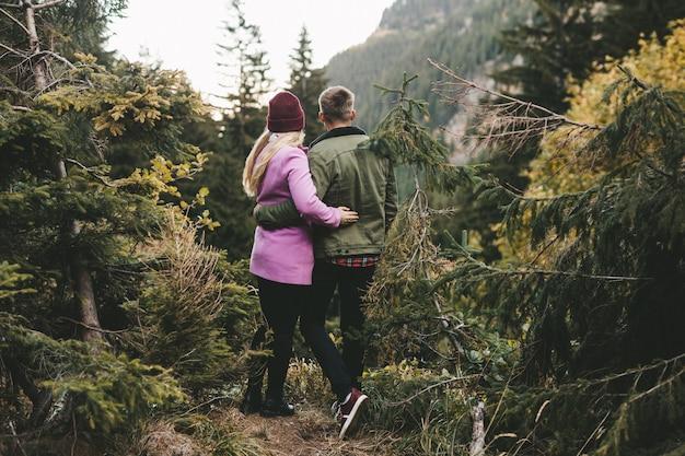 Una coppia guardando la foresta in montagna