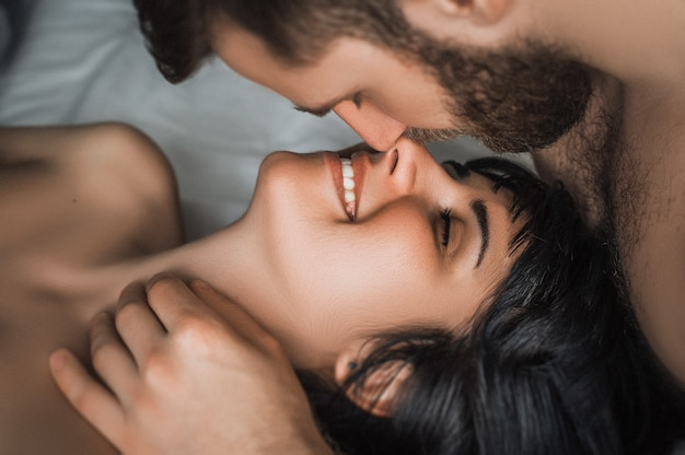Una coppia innamorata fa l'amore a letto. ragazzo e ragazza baci. coppia di innamorati che fanno sesso. coppia a letto. notte di nozze. fare l'amore. amanti a letto. sesso tra un uomo e una donna. amore. bacio. tenerezza