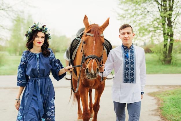 Una coppia innamorata in abiti blu festosi tiene un cavallo dietro la briglia e guarda l'obiettivo