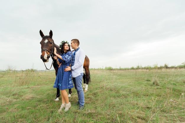 Una coppia innamorata si trova nell'abbraccio e la ragazza tiene un cavallo per una briglia sullo sfondo di un prato
