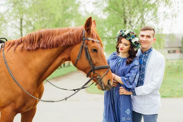 Una coppia innamorata si trova vicino a un bellissimo cavallo e la ragazza lo tiene per una briglia