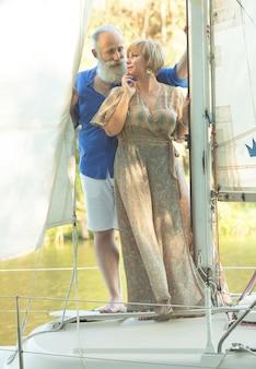 Una coppia senior felice che naviga e che si siede alla ruota di una barca a vela sul lago.