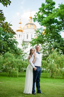 Una coppia sposata sta camminando e abbracciando nel parco.