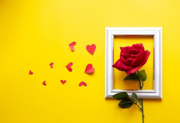 Una cornice bianca e cuori incastonati su uno sfondo giallo e una rosa rossa. san valentino sullo sfondo.