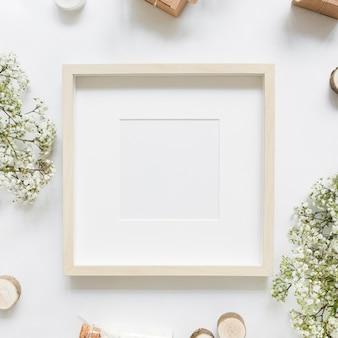 Una cornice bianca vuota circondata da fiori e scatole regalo