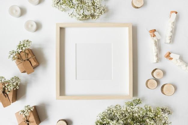 Una cornice bianca vuota circondata da scatole regalo; candele; tronco d'albero; provette marshmallow e fiori baby's-breath su sfondo bianco