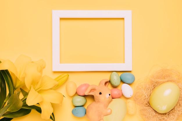 Una cornice bianca vuota decorata con fiori di giglio; figurina di coniglio e uova di pasqua su sfondo giallo