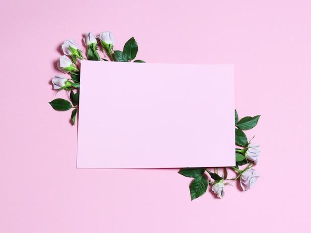 Una cornice con rose di fiori bianchi su sfondo rosa