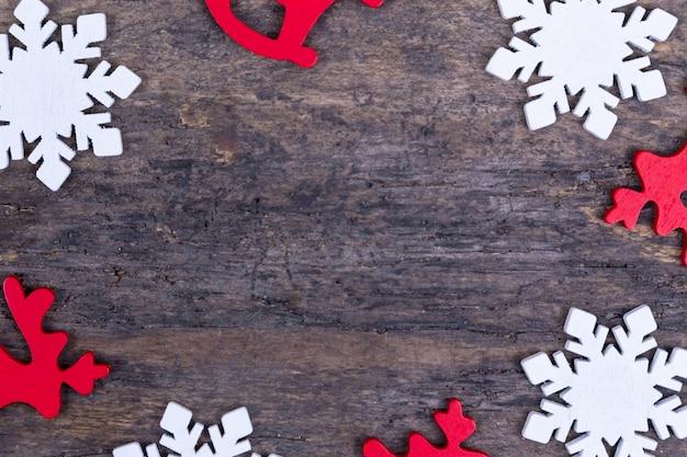 Una cornice di decorazioni natalizie in feltro poste su uno sfondo di legno con copia spazio. natale cervo, fiocco di neve, stella