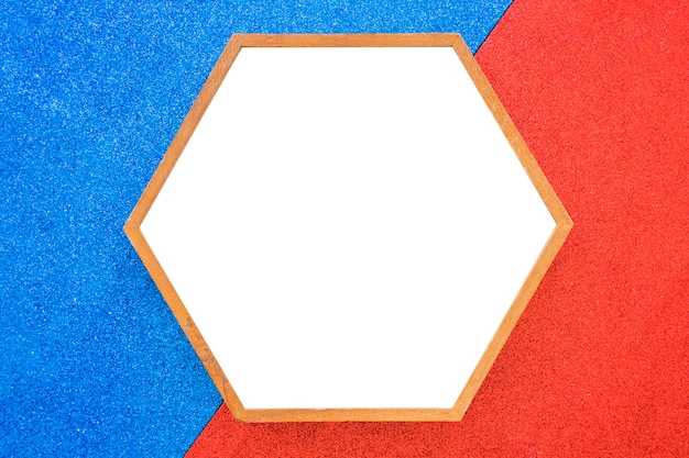Una cornice di esagono in legno vuota su sfondo rosso e blu